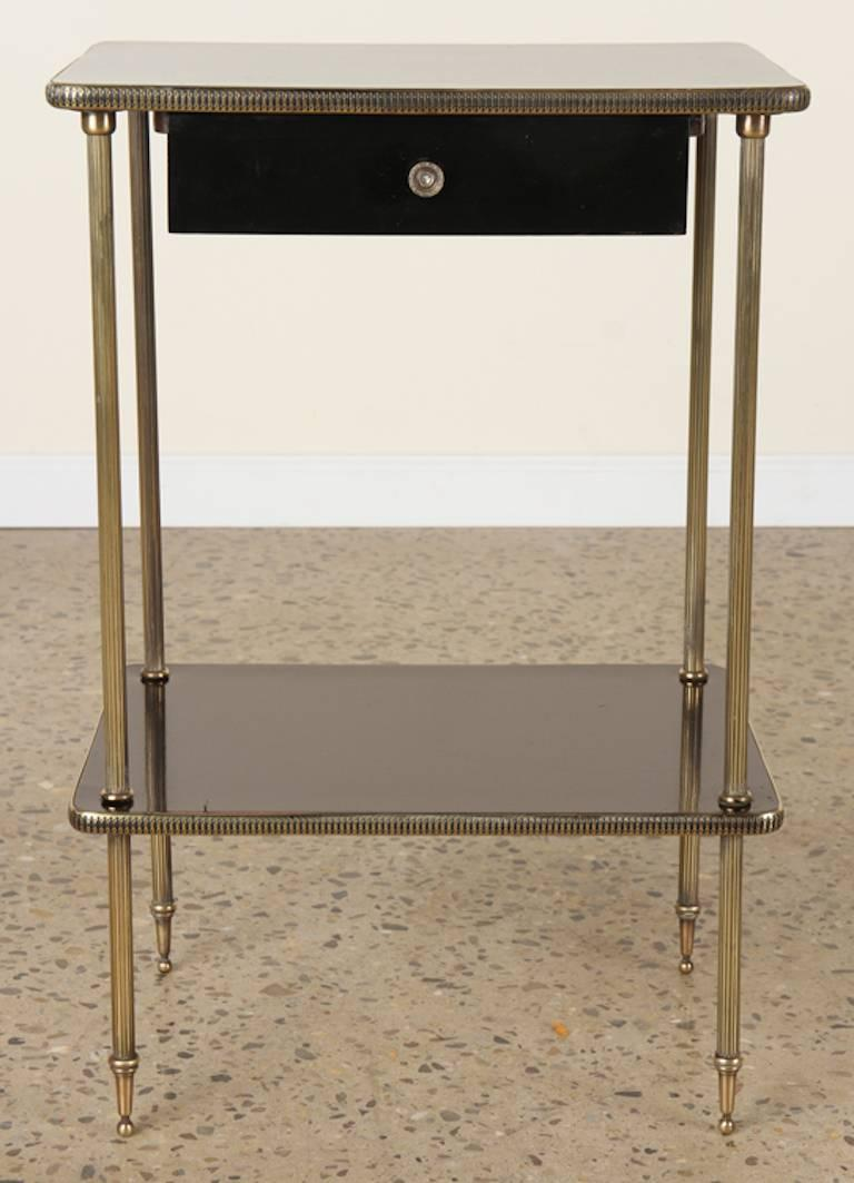 This graceful pair of black lacquer and brass side tables feature a single drawer with brass legs, banding and pulls. Perfect for bedside tables - nightstands. circa 1950.