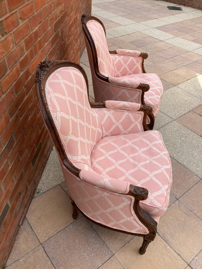 Beautiful upholstered pair of French styled bergere chairs with fully carved wood frames featuring acanthus leaves, fluted legs and flowers. White on pink fabric is in a diamond pattern. Seat slip covers are removable. Cushions are down and feather