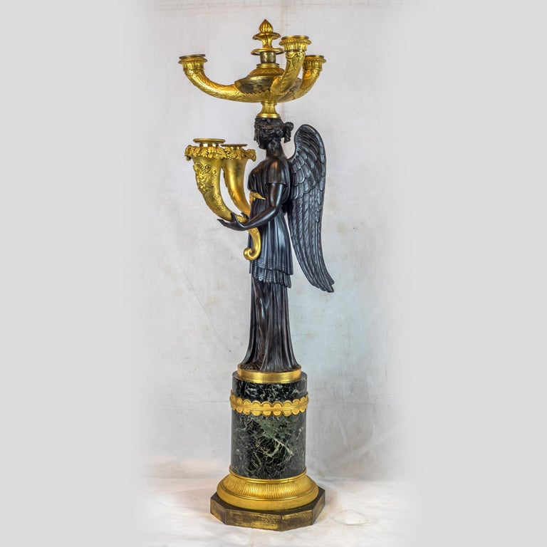 An Elegant pair of Empire Patinated and gilt bronze five-light candelabras. 