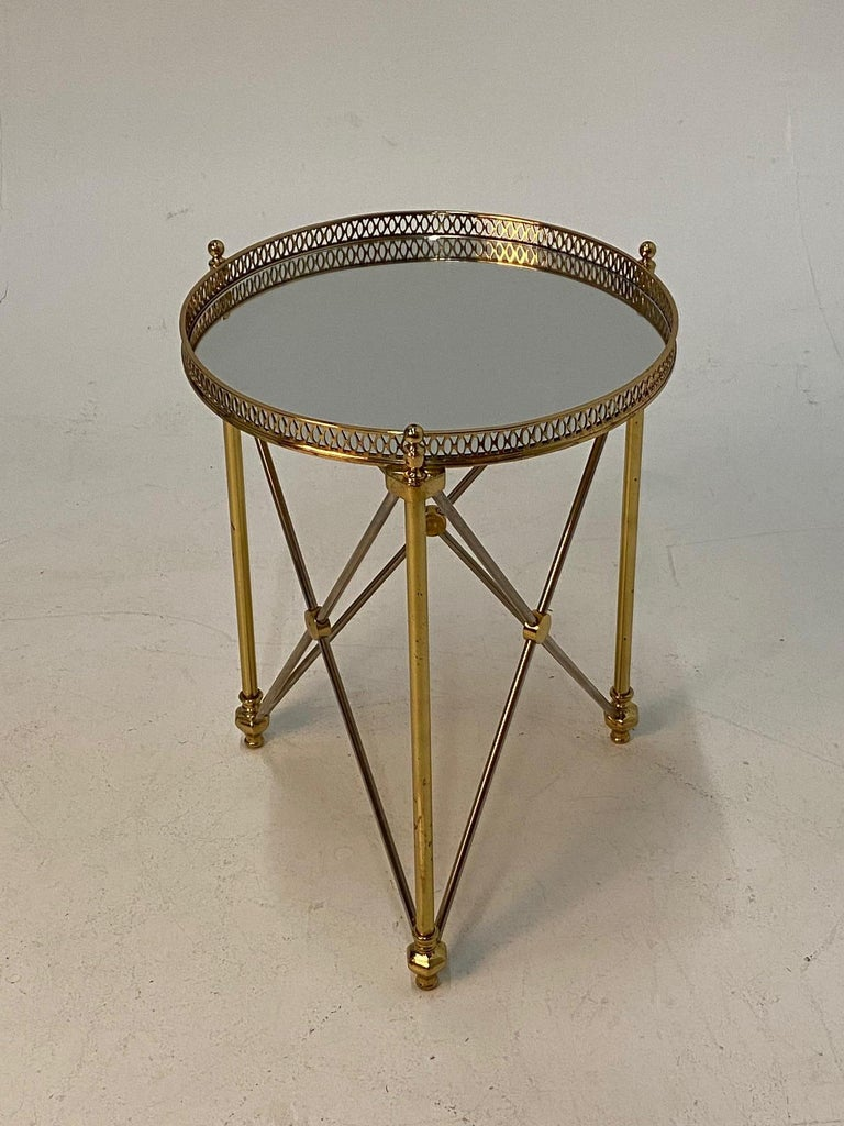 Elegant round martini table in the style of Maison Jansen having polished steel and brass neoclassical design, pierced gallery and mirrored top.