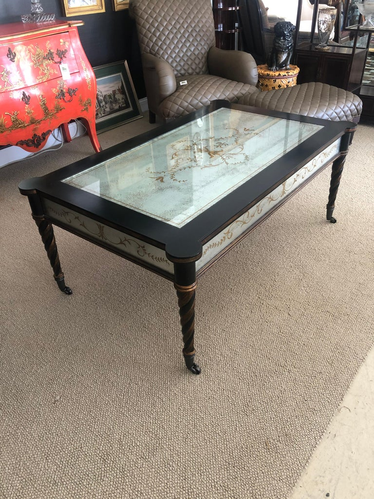 Impressive designer coffee table having ebonized base with twisted tapered legs and gorgeous églomisé mirrored inset top and sides. Legs also have gilded bronze embellishments and terminate in brass casters.