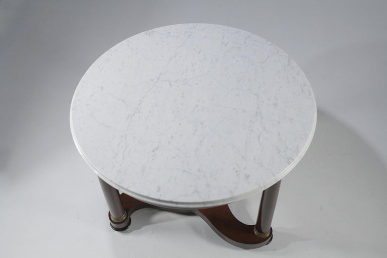 Stately round Regency style center table having a handsome mahogany base with 3 sided stretcher between the ebonized tripod legs, a beautiful white marble top, and bronze decorative mounts.