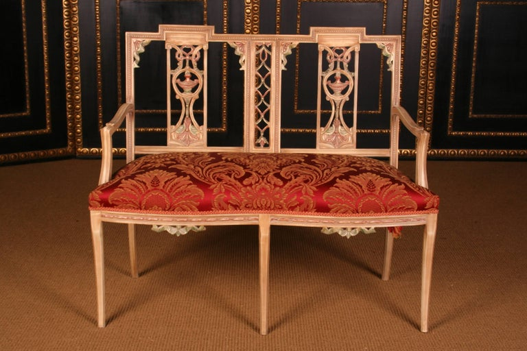 Solid beechwood, colored. Cambered and carved frame on saber-shaped, tapering legs. Rising armrests. Shield-shaped backrest frame with Fine carving. The seat and backrest are finished with a Classic Classic upholstery.  Measures in