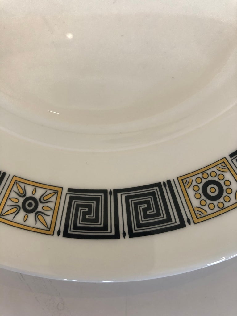 A delicious set of 12 Wedgewood dinner service plates having black and gold border with fabulous Greek key motife.