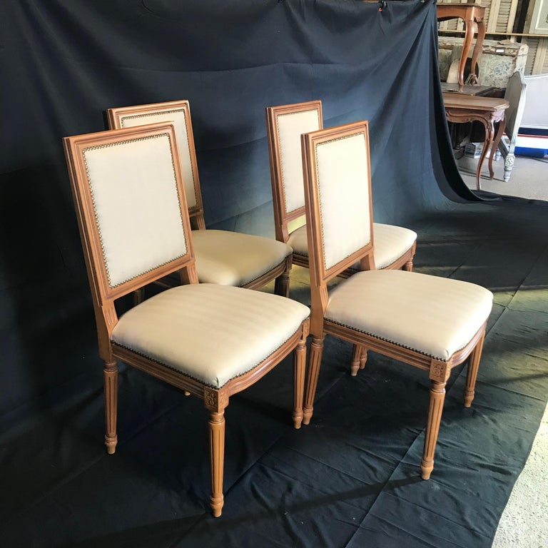 Set of four French Louis XVI style chairs with walnut frames with lovely fluted legs with classic cubic blocks decorated with florets. Upholstered in beige fabric and finished with decorative tacking typical of the period.