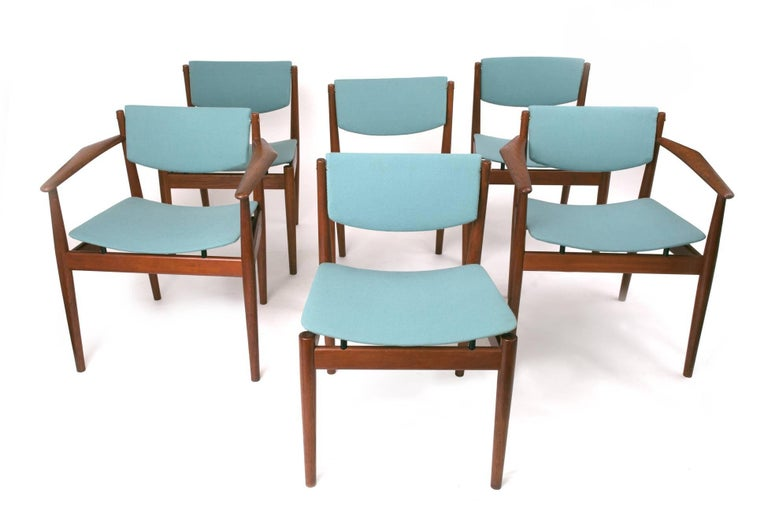 A set of six airy, elegant model 197 dining chairs by Finn Juhl for France & Son. The set includes four side chairs and, uncommonly, a rare pair of armchairs with triangular armrests that embrace the form of the human body. In teak with beautifully