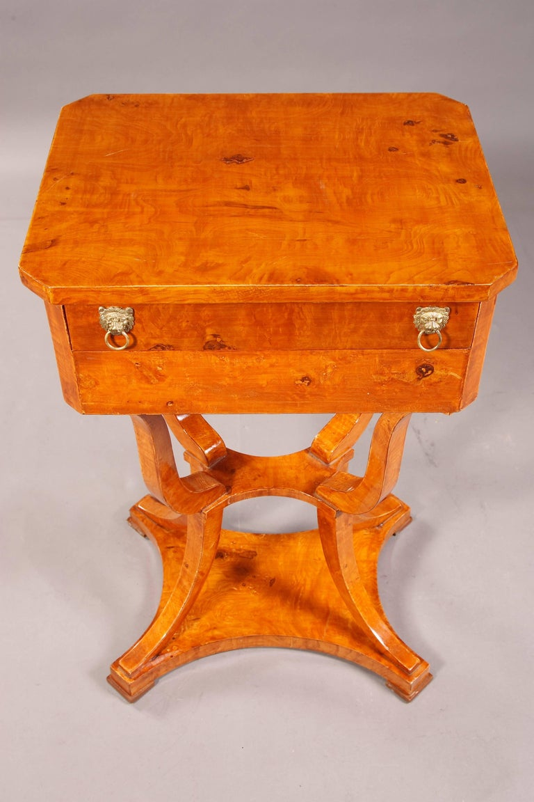 Ash root on solid beech. On strongly curved, over corner standing legs, connected by slightly intervening intermediate compartment. Outstanding saber-shaped legs on four-sided base plate on the washers. Two-bar frame base, upper drawer with