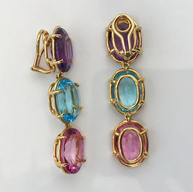 18kt Yellow Gold Elegant Three Stone Drop Earrings with faceted oval Amethyst and Blue Topaz and Pink Topaz  The Earrings measure 2 1/4 in length. The earrings can be made for Clip Earring or Pierced Earrings. They can also be custom made with any