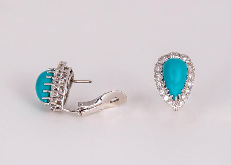 Beautifully matched turquoise are framed with brilliant cut diamonds in this elegant pair of earrings. The turquoise makes diamonds possible day to night. Just shy of 7/8's of an inch in length. 2.00 carats in diamond weight.