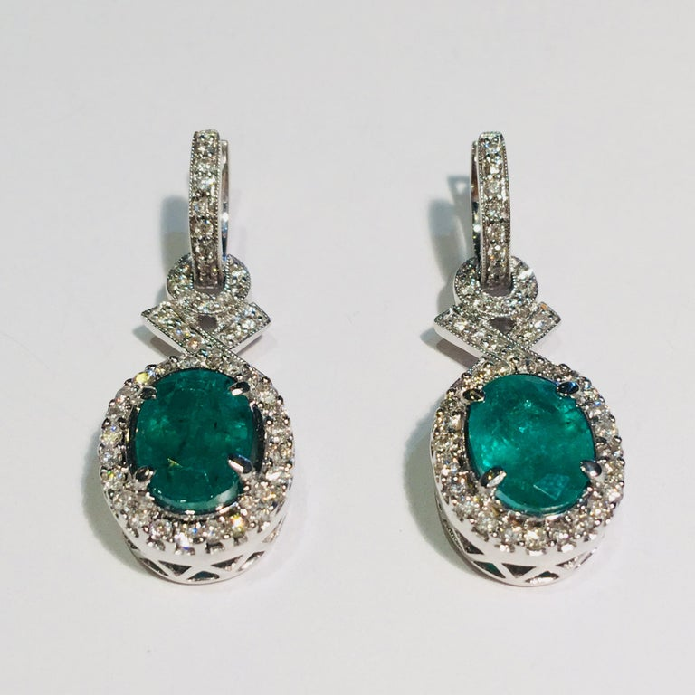 Elegant, dangling emerald and diamond halo 18 karat white gold estate earrings feature large, prong set, bright green, oval cut emeralds surrounded by sparkling halos of prong set round brilliant diamonds and accented by pave set round brilliant