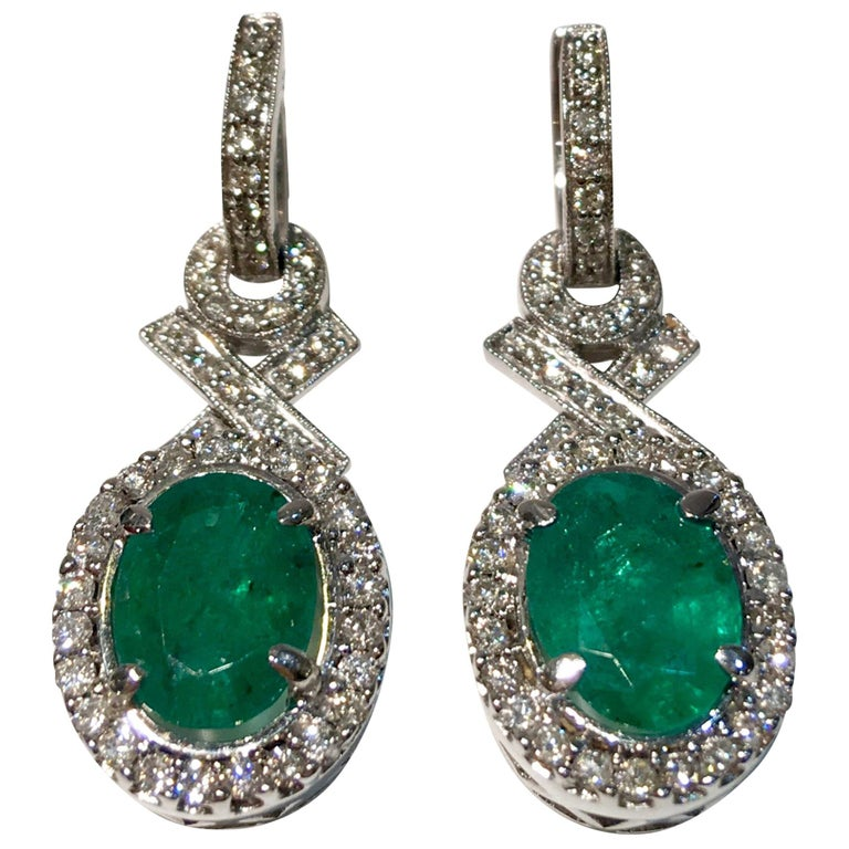 "Elegant ""XO"" Oval Emerald and Diamond Halo 18 Karat White Gold Drop Earrings For Sale"