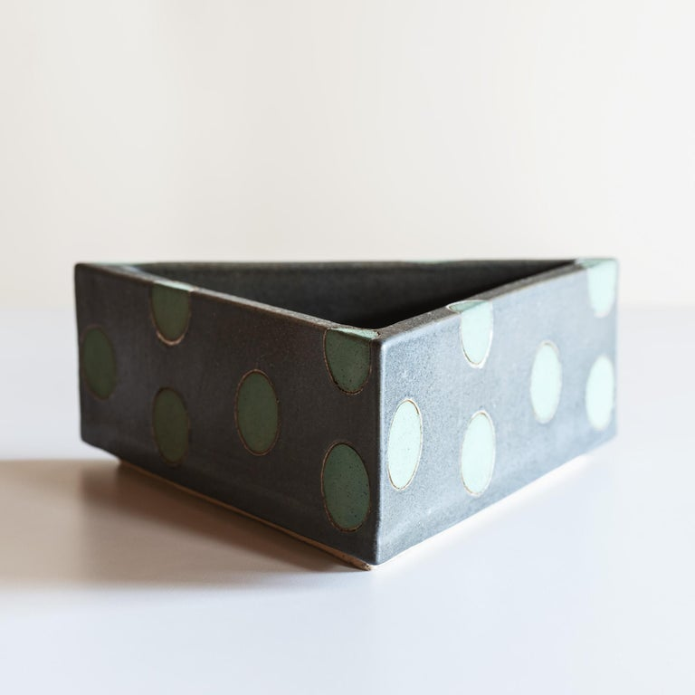 Stoneware vessel with green polka dots on earthen grey background.