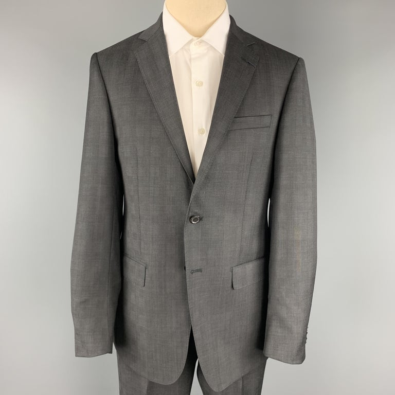 ELOE TAHARI suit comes in charcoal glenplaid wool and includes a single breasted, two button sport coat with notch lapel and matching flat front trousers. Made in Canada.  New with Tags. Marked: 40 REG  Measurements:  -Jacket Shoulder: 17
