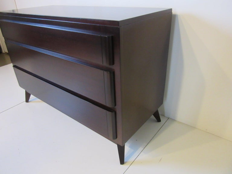 A dark ebony toned three drawer dresser chest with nice deep drawers for storage , solid and well crafted with a tight design look that would work with any decor manufactured by the RWAY  furniture company from their R Way Modern Collection .