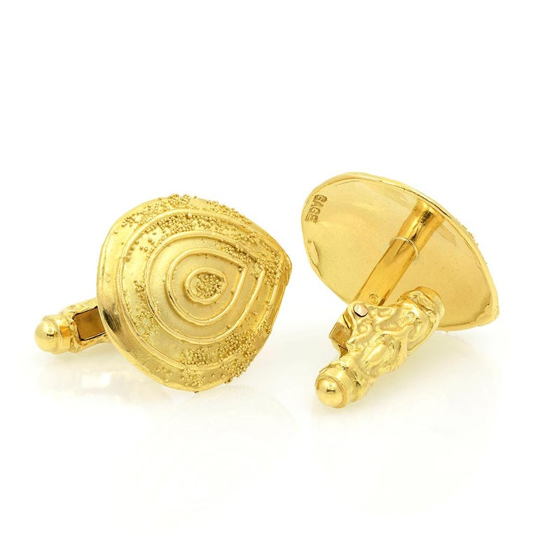 From designer Elizabeth Gage, these 18 karat yellow gold cufflinks are a teardrop shape with a granulated finish and ridges that radiate from its center. The cufflinks measure 22.74 mm long by 19.43mm wide. -18k Yellow Gold -Granulated