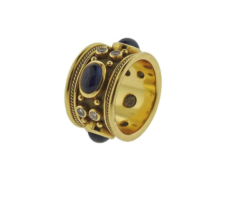 18k yellow gold band ring by Elizabeth Gage, created for Templar collection, set with blue sapphire cabochons and approx. 0.36ctw in diamonds. Ring size 6.5, measures 13.5mm wide, weighs 14 grams. Marked:  Gage, Gold Assay Marks.