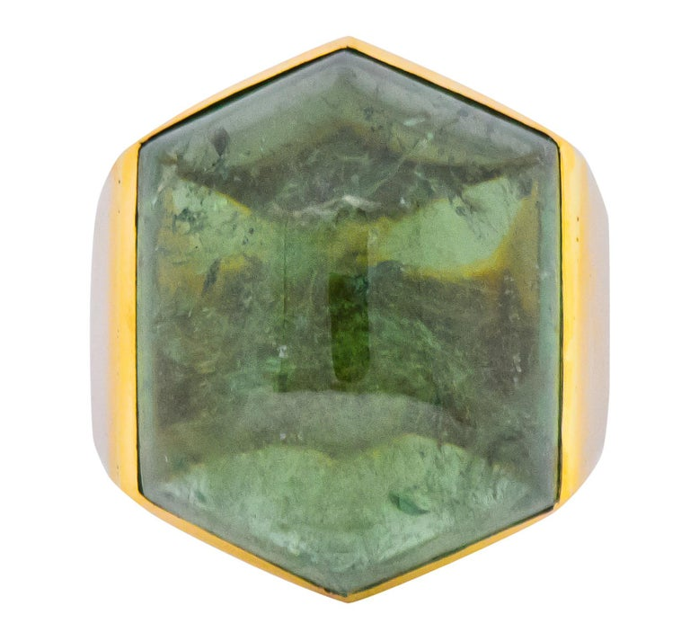 Centering a hexagonal cabochon tourmaline measuring approximately 1 1/4 x 1 1/8 inch, transparent medium-light forest green color  Bezel set into high polished 18 karat gold mount and shank  Stamped 750 for 18 karat gold with British hallmarks and