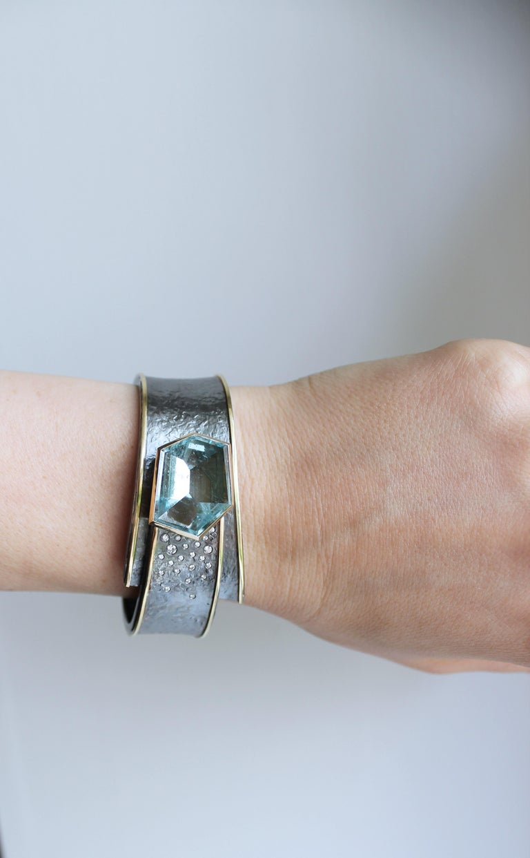 One of a Kind Cyclone Cuff Bracelet handcrafted by jewelry artist Elizabeth Garvin featuring a spectacular mirror-cut aquamarine set in hand-hammered oxidized sterling silver and 18k yellow gold with embedded round brilliant-cut white diamonds and