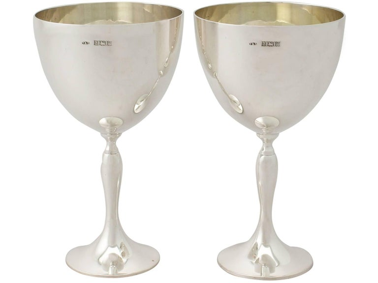 An exceptional, fine and impressive pair of vintage Elizabeth II English sterling silver goblets; an addition to our range of wine and drink related silverware  These exceptional vintage Elizabeth II sterling silver goblets have a plain bell