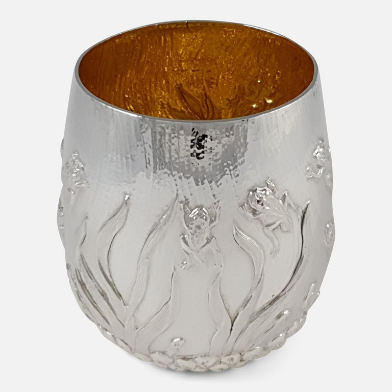 An Elizabeth II sterling silver gilt beaker made by Garrard & Co. Limited. The beaker, with gilt wash interior, is of tapering cylindrical design, depicting a chased scene of frog spawn to the base, leading to tadpoles and frogs emerging swimming