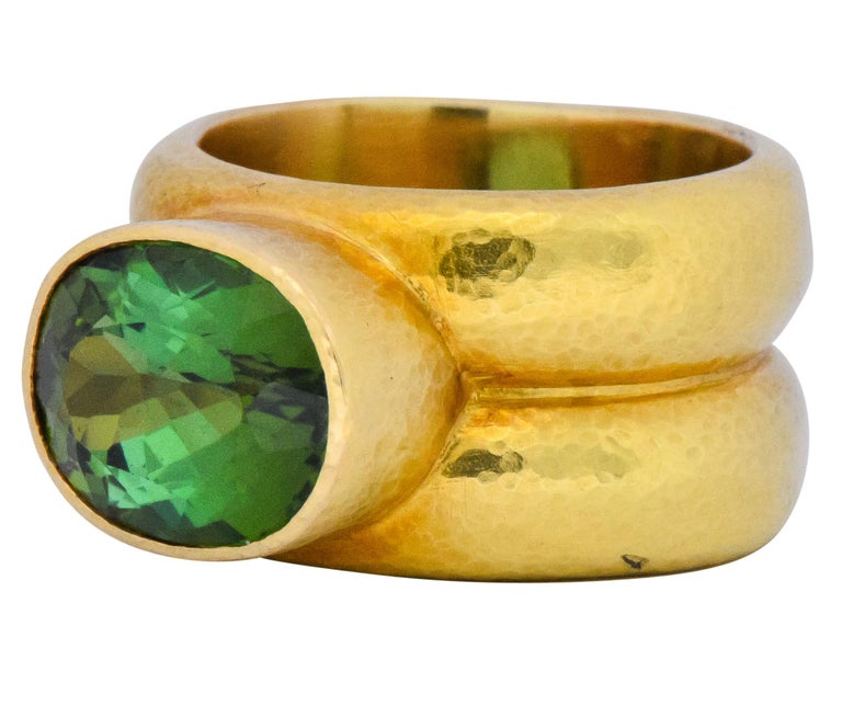 Centering an oval cut tourmaline weighing approximately 4.00 carats  Displaying lively blue and yellow green hues  Bezel set in hammered gold double shank  Tested as 18 Karat  Ring Size: 5 1/2 & not sizable  Top Measures: 9 mm and sits 7 mm