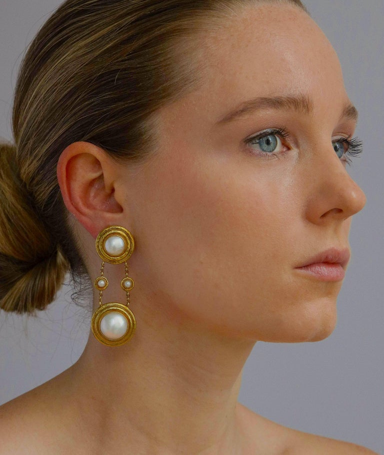 Elegant and fashionably long Elizabeth Locke ear clips of 18K gold set with lustrous mabe pearls both youthful and sophisticated with a hinged post for an added pierced option. The top pearl measuring 3/4 inch diameter and the lower 1 inch with a