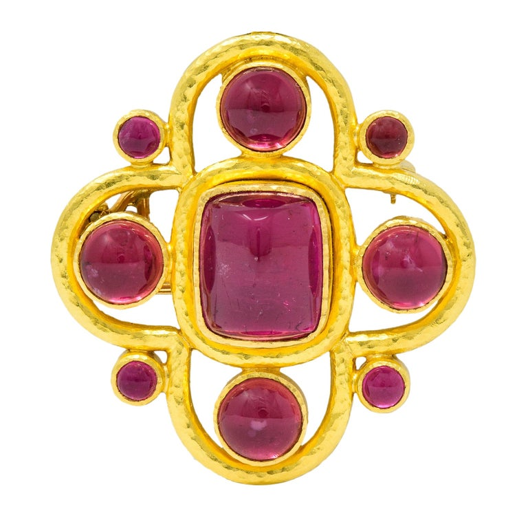 Pendant brooch is designed as a clover-like quatrefoil with a hammered finish  Centering a rectangular sugarloaf pink tourmaline measuring approximately 13.5 mm x 11.0 mm  Surrounded by round pink tourmaline measuring 12.0 mm and 3.5 mm  All a very