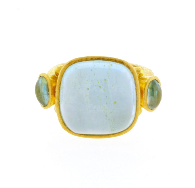 From Elizabeth Locke, a light blue aquamarine set in hammered 19 karat gold ring ♦ Designer: Elizabeth Locke   ♦ Metal: 19 karat ♦ Gem stone:   Aquamarine  14mm X 14mm ♦ Gem stone: 2 Oval Aquamarines 4mm X 6mm ♦ Circa 2014 ♦ Size 6, Resizable ♦