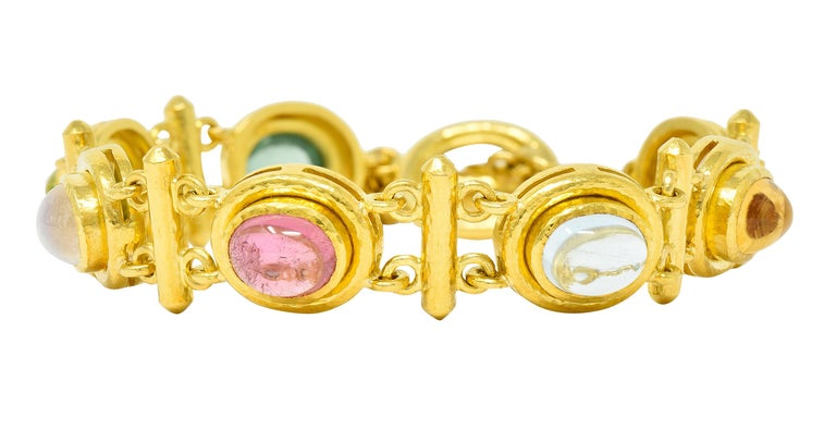 Bracelet is comprised of bezel set links alternating with bar spacer links  Featuring oval cabochons of tourmaline, citrine, moonstone, labradorite, peridot and other  With a hammered gold finish throughout  Completed by a toggle style clasp -