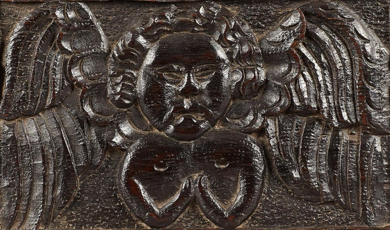 Late Elizabethan oak angel panel, English, circa 1580 - 1600  The relief carved winged angel set within a wavy chip carved border, with good rich,  dark patination.