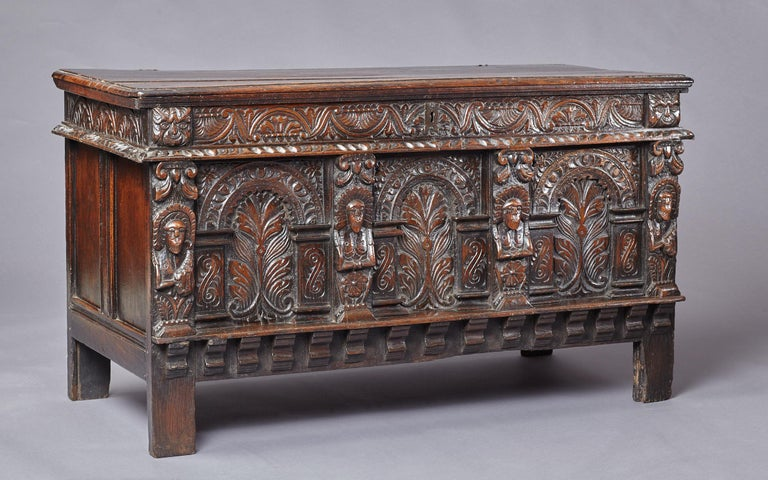 Late Elizabethan oak chest, West Country, Somerset, circa 1600.  The two plank top retaining original wrought iron loop hinges above a floral lunette carved frieze flanked by a pair of Green man masks, above three arcaded panels carved with foliate