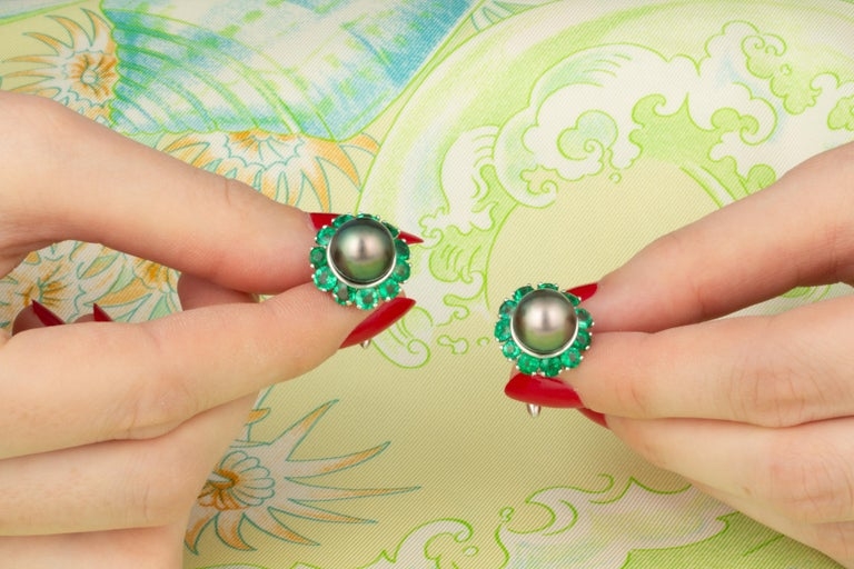 The emerald and pearl cufflinks feature two lustrous pearls from the waters of French Polynesia. The untreated pearls have a diameter of 10mm, and display