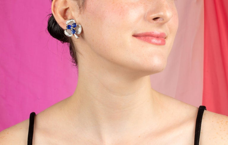 This pair of blue sapphire and diamond earrings features a flower design with oval cut faceted Ceylon sapphires for a total weight of 7.93 carats. The sapphires are set en tremblant, a technique rarely practiced today. The design is complete with a