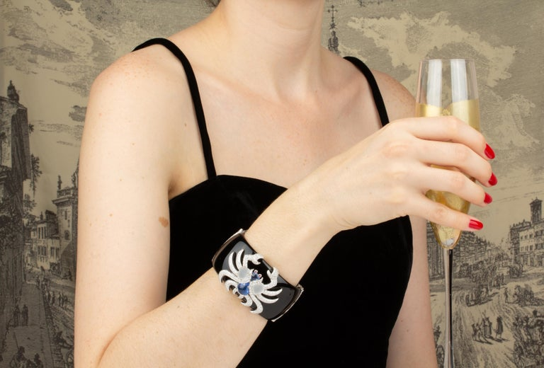 The Cancer Zodiac cuff bracelet consists of a custom-cut natural black agate base with two well-engineered hinges set with diamonds. The two extremities of the cuff are finished with a crescent of round diamonds. The sculpture en relief is set en