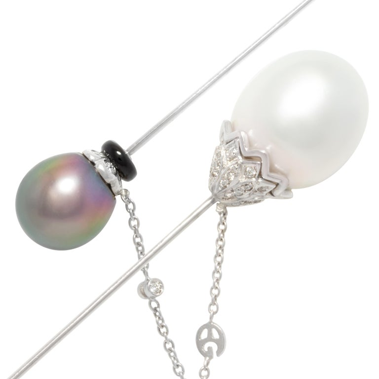This stick pin features an 19mm South Sea pearl in a crown of round diamonds, and a 12mm Tahitian pearl decorated with an onyx ringlet. The chain is accented with diamond motifs. The total weight of diamonds of top quality is 1.50 carats (F/G-VVS).