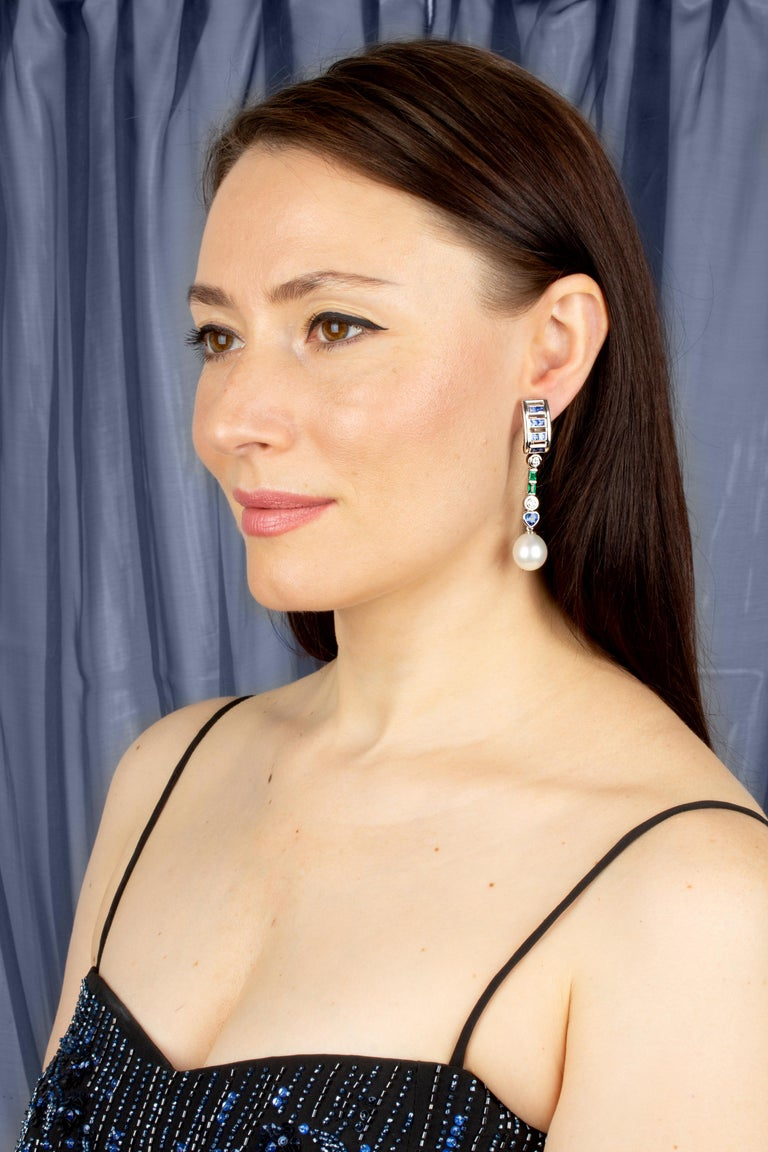 This pair of earrings features a hoop-like design on the ear set with faceted blue sapphires. The tops suspend an articulated column set with round diamonds, emeralds, and heart shape sapphires. The total weight of blue sapphire is 4.02, and of