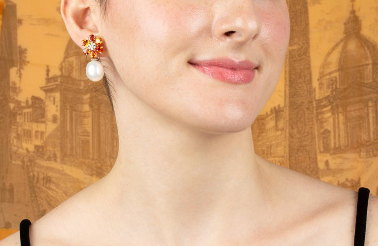 The sapphire and pearl earrings feature a flower design on the ear with 8.40 carats of oval cut faceted orange sapphires. The tops suspend 2 South Sea pearls of 15mm diameter. 0.35 carats of round diamonds complete the design. All of our pearls are