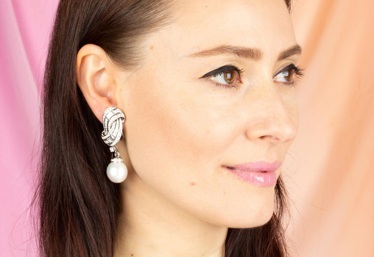 This pair of South Sea pearl and diamond earrings features a swirl design on the ear with 4.86 carats of round diamonds accented with 4 large custom-cut baguette diamonds (1.24 carats). The tops suspend 2 very fine detachable South Sea pearls of