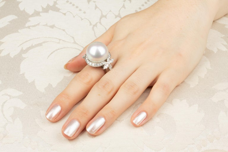 The South Sea pearl and diamond ring features a large pearl of 18mm diameter. The pearl is untreated. It displays a splendid nacre and its natural color and luster have not been enhanced in any way. The pearl is flanked by a leaf-like design with