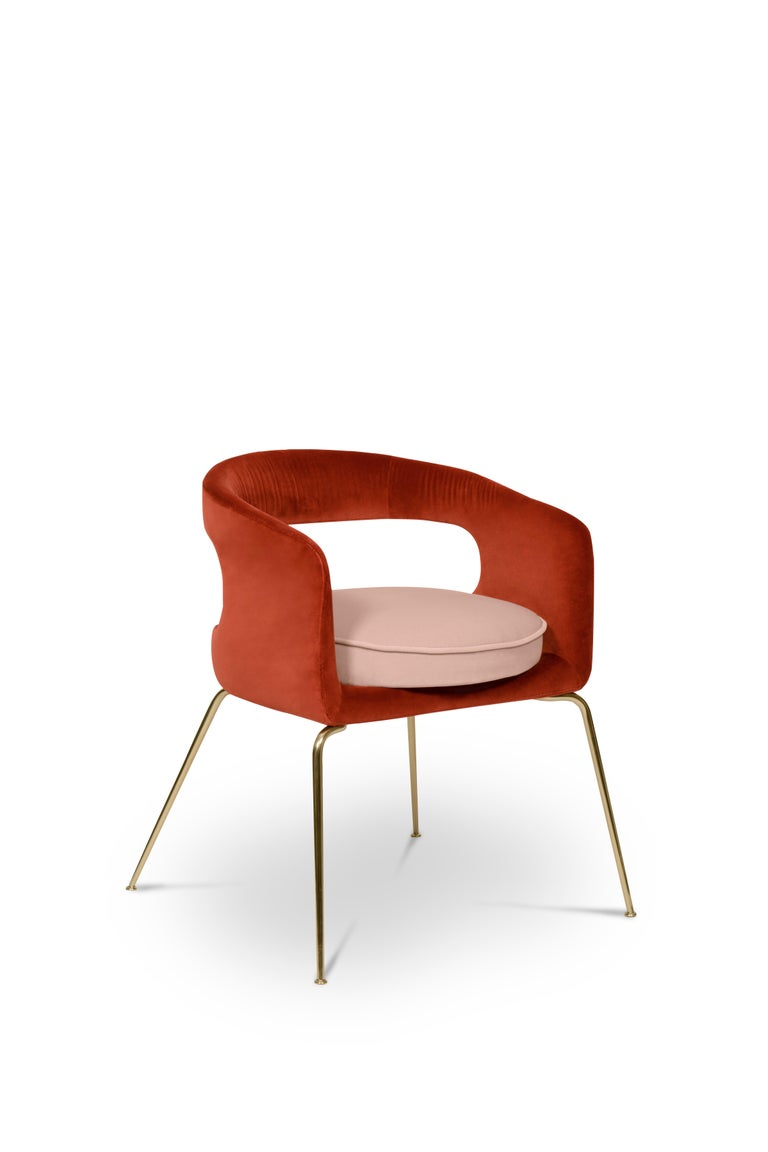 Ellen is a fanciful dining chair full of luxurious features. Its distinctive open curved back is extremely sculptured and it contrasts with the slim legs made of polished brass. It is upholstered in velvet and has mixed tones both on the back and