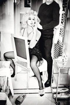 Filmstar Monica Bellucci  in a small black dress with a man in a bathroom