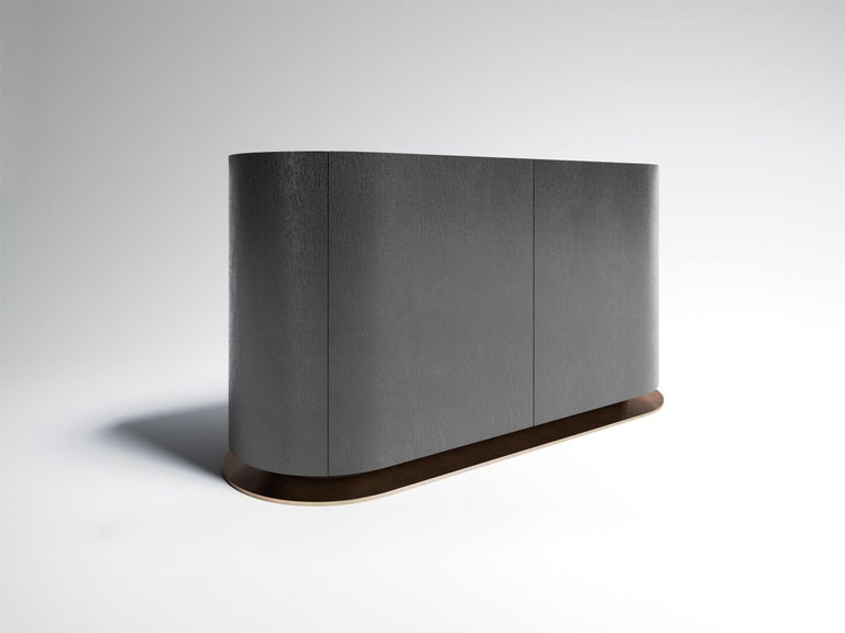 Éllipse sideboard has a Silver Sucupira veneer semi gloss exterior and black lacquered interior with one internal shelf. It sits on a recessed wide bronze base plate and features bronze inlay all around the top. Available in a variety of material.