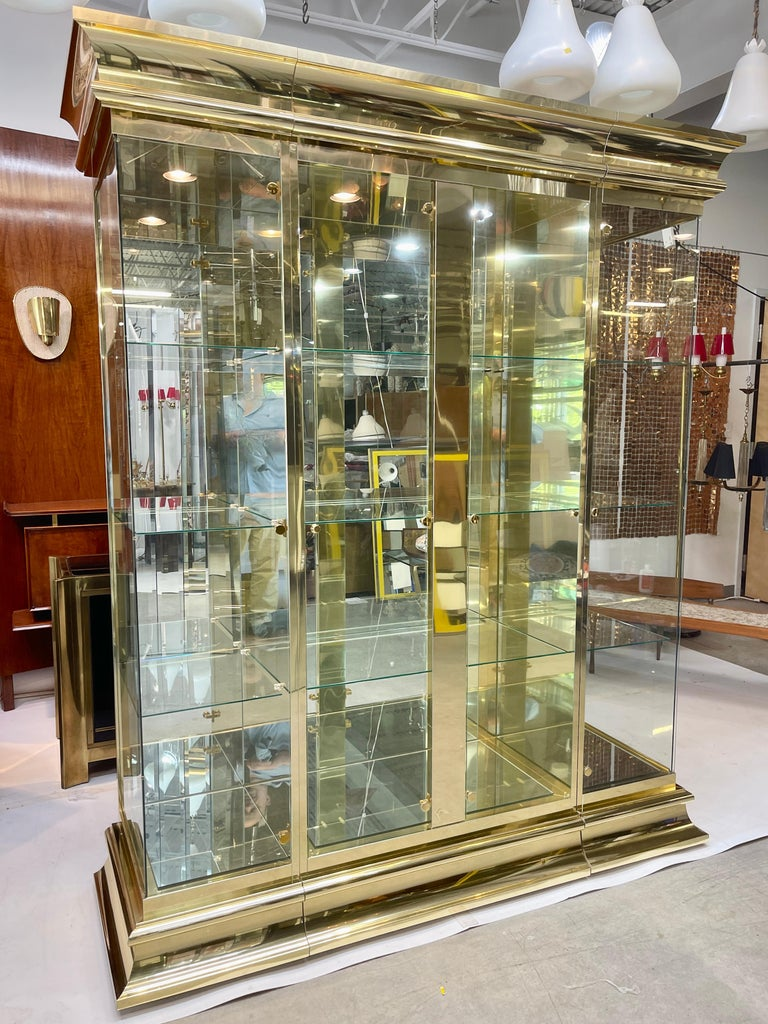 Brass and mirror three section illuminated curio display showcase designed by O. B. Solie in 1986 for Ello Furniture Manufacturing Corp. of Rockford, IL as part of the LaCage Collection.  Nine glass shelves with engraved plate slots. Mirror floors