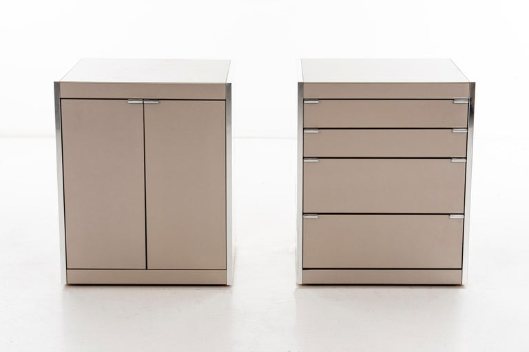 Three-drawer and two-door, cases by Guy Barker for Ello. Shown in titanium glass with polished chrome and silver mirror sides. Adjusting levellers.