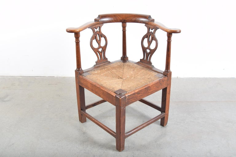 Elm Chippendale corner chair with rush seat, circa 1780-1820. Most likely English. As with many pieces of this age, there have been some repairs over the years. Most notably, a few of the original square pegs have been replaced with round pegs.