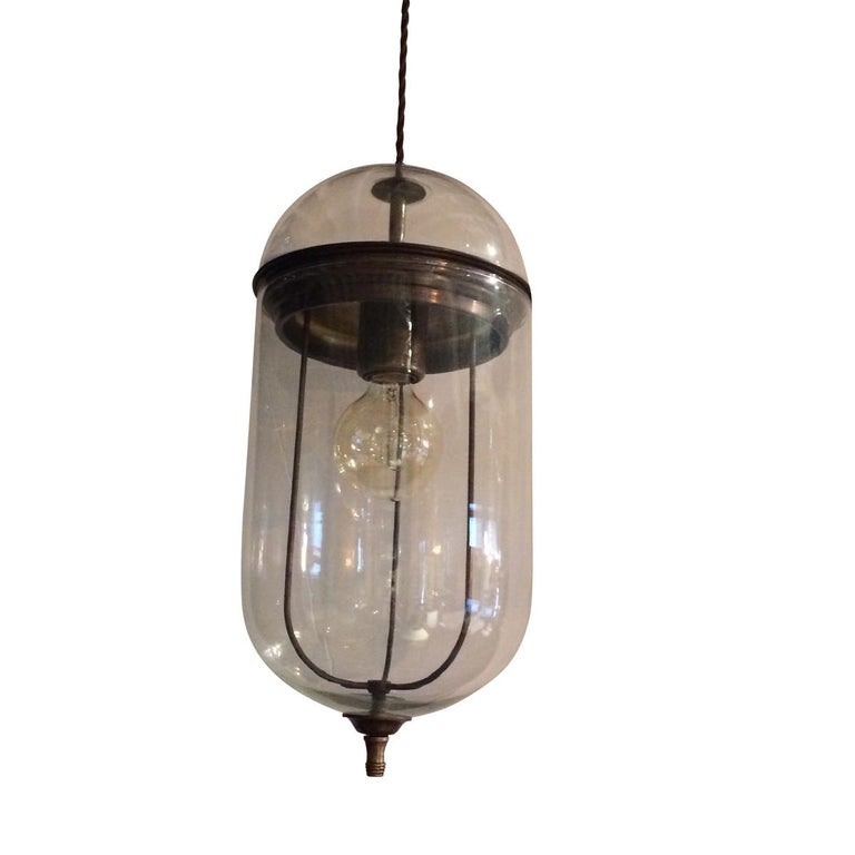Contemporary pair of Italian bronze and elongated glass pendant lights.