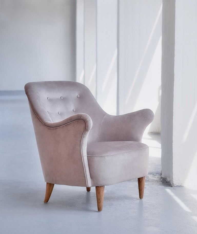 This rare armchair was produced by AB Elsa Gullberg in the late 1930s. The organically shaped arms of the chair and the carved, tapered legs give the chair a sculptural and modern feel. The chair is upholstered in a taupe/grayish velvet fabric, the