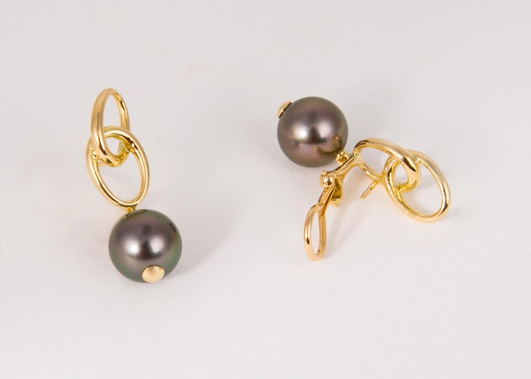 Elsa Peretti has always proven less is more. Rich Tahitian pearls are suspended below elegant geometric loops. Simply Chic !!! 1 3/8's in length. The pearls are 10.6mm each.