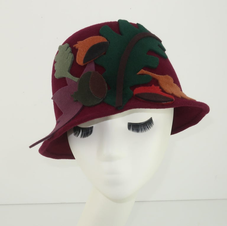 Belgian designer, Elvis Pompilio, offers a touch of autumn with this 1990's wool felt bucket hat creation.   The base of the hat is a deep burgundy red which is decorated with felt appliques in abstract shapes of leaves and acorns, all in shades of