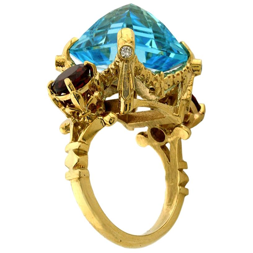 Elysium Ring in 9 Karat Yellow Gold with Blue Topaz, Garnets and Diamonds